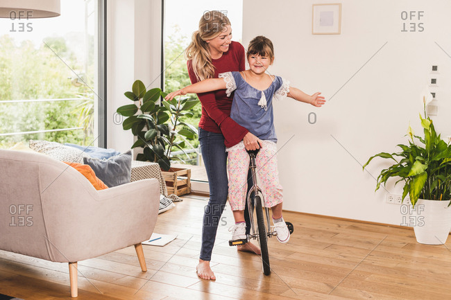 Mother supporting daughter on unicycle at home