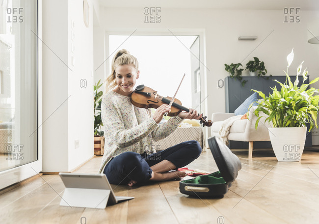 Woman with tablet sitting on the floor at home playing violin