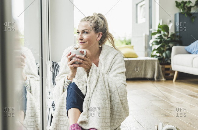 Woman wrapped in a blanket sitting at the window at home drinking coffee