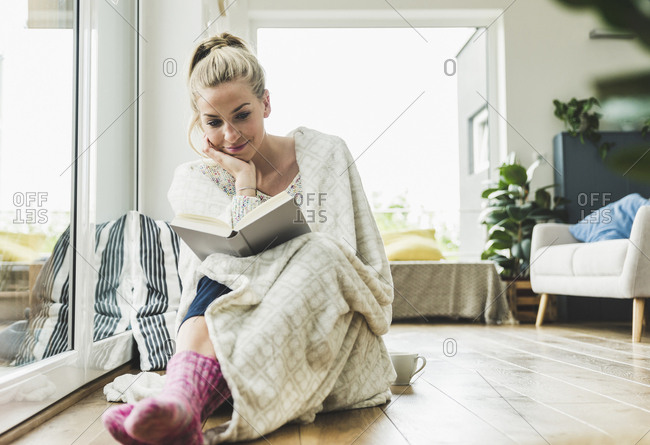 Woman wrapped in a blanket sitting at the window at home reading a book