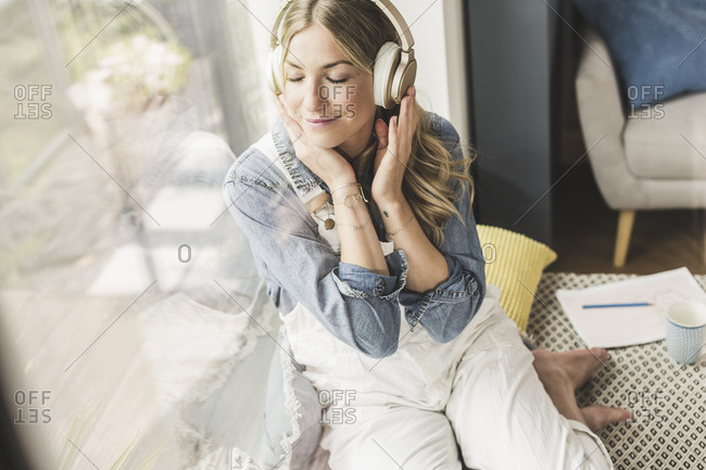 Woman sitting at the window at home listening to music with headphones