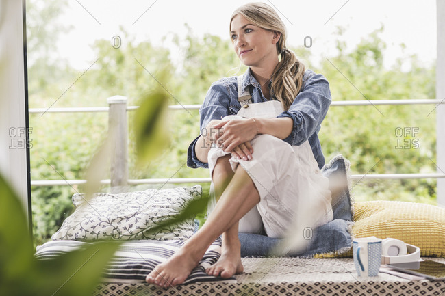Relaxed woman sitting at the window at home
