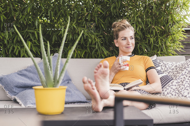 Relaxed woman sitting on couch on terrace at home drinking coffee