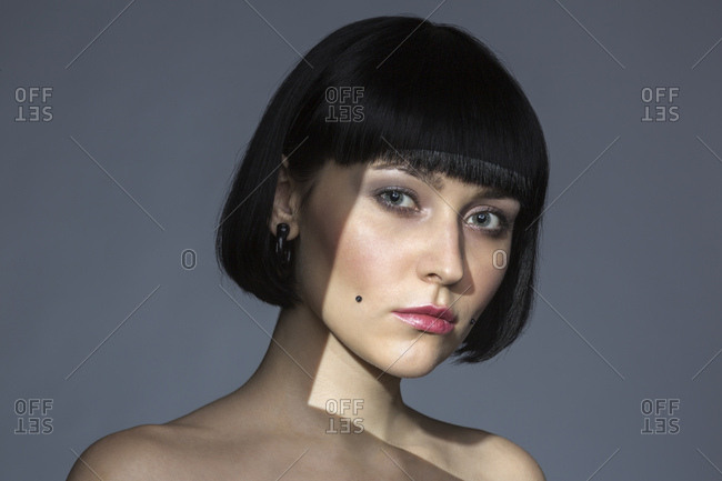 Portrait of young woman with cheek piercing
