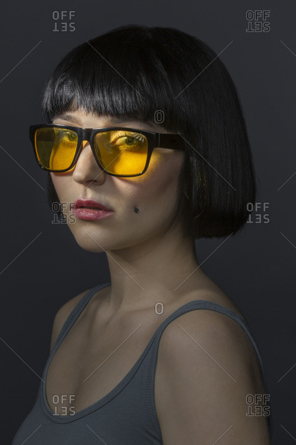 Portrait of young woman with cheek piercing and yellow glasses