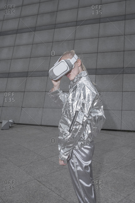 Girl in silver suit. looking through VR goggles in futuristic city