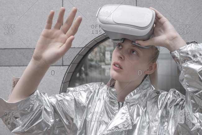 Girl in silver suit looking through VR goggles- watching her hand