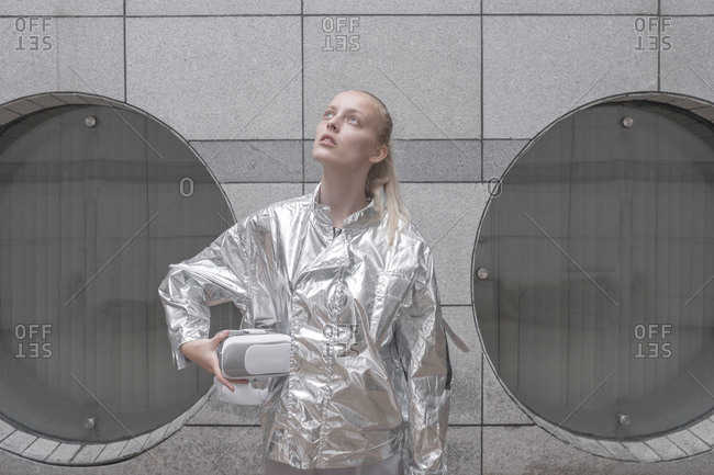 Girl in silver suit carrying VR goggles under her arm