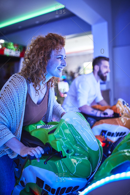 Woman playing and having fun with a driving simulator in an amusement arcade
