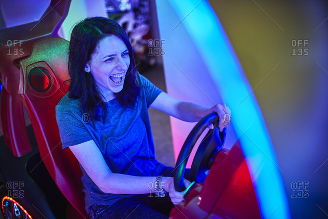 Excited woman playing and having fun with a driving simulator in an amusement arcade