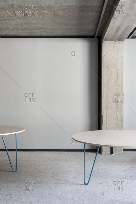 Two tables on hairpin legs in a minimalist designed concrete room