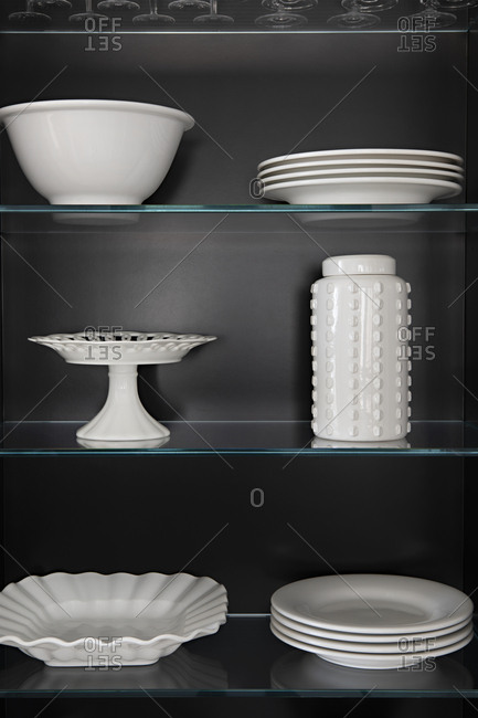 White ceramic dishes arranged neatly on glass shelves