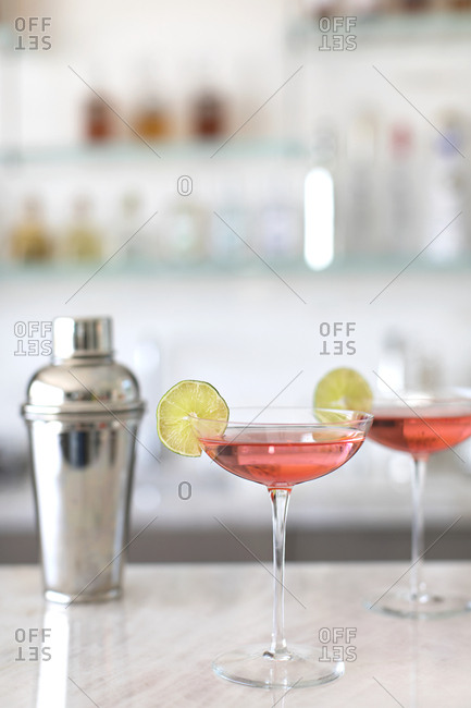 Two pink cocktails garnished with lime