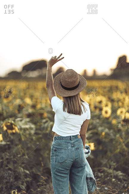 Young woman standing in a sunflower field holding her hands up in a peace sign