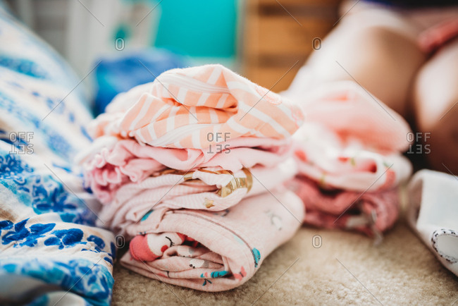 Piles of freshly washed and folded baby girl clothes