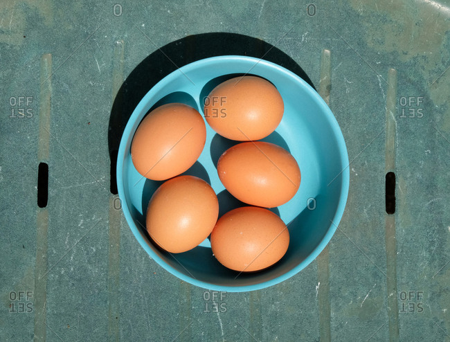 Overhead view of five brown eggs in a blue bowl