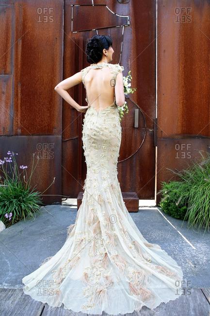 Bride modeling her wedding gown in front of large door
