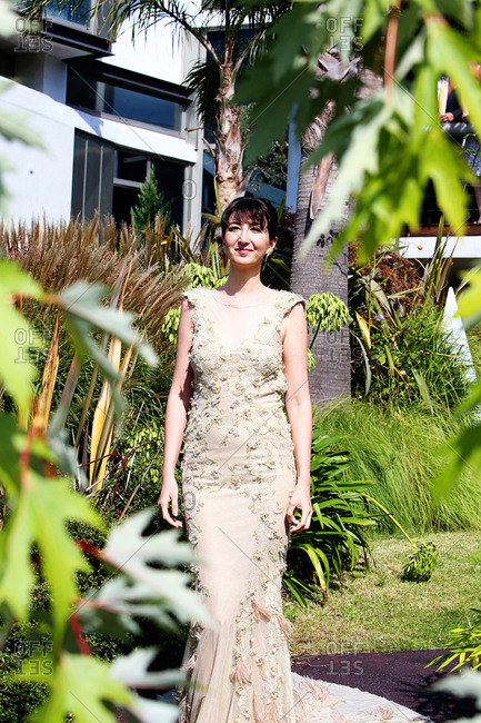Bride sun blasted amongst palm trees waiting for groom