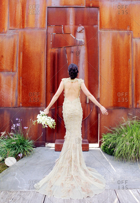 Back view of bride with bouquet in custom lace wedding gown