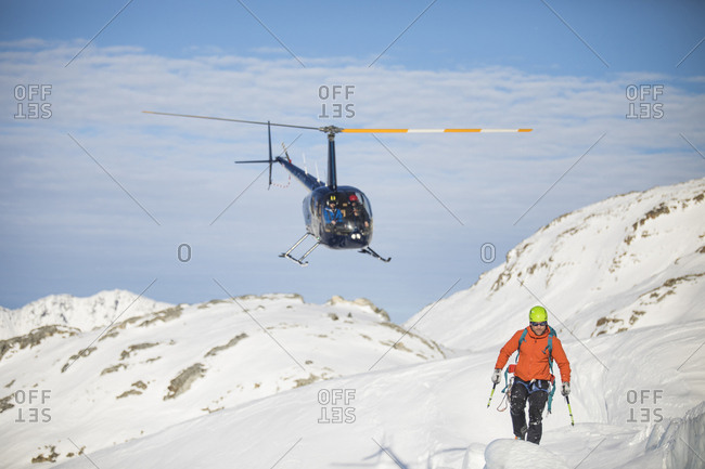 Helicopter approaches mountaineer in a snowy landscape.