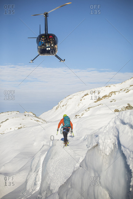 Helicopter approaches mountaineer in a mountain landscape.