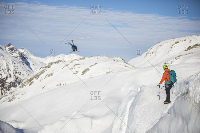 Man directing helicopter on snow-covered mountain