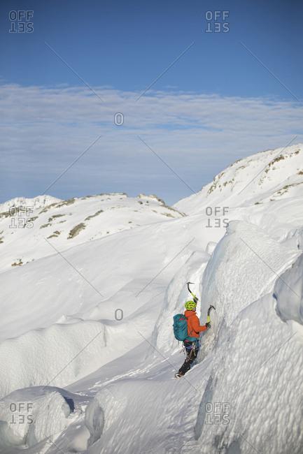 Man ice climbing on glacial seracs in the coast mountain range.