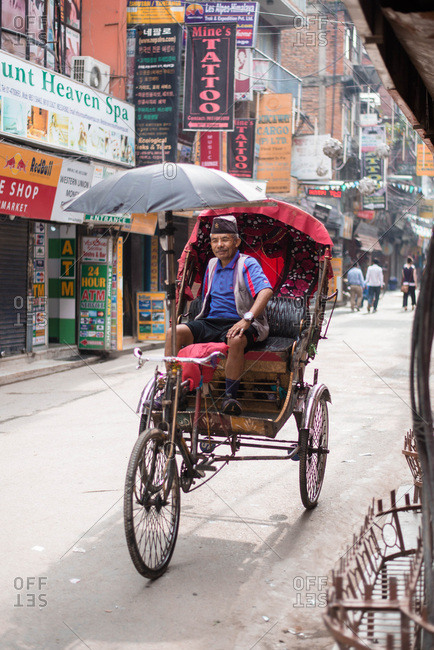 Kathmandu, Nepal, Southeast Asia - September 26, 2018: Smiling man driving bicycle cart through streets of Nepal
