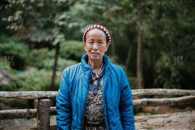 Langtang, Nepal - September 30, 2018: Friendly woman posing in mountains in front of fence