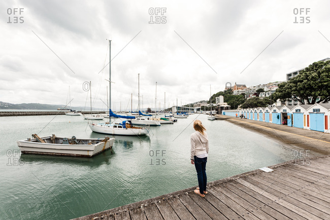 Tween girl looking at sailboats in Wellington, New Zealand