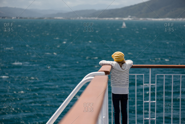 Girl in yellow knit hat looking over railing at the ocean