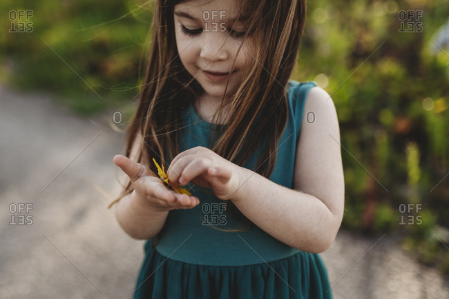 Mid-level view of little girl holding flower and smiling