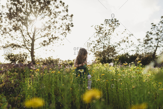 Landscape of little girl looking down in field of spring flowers