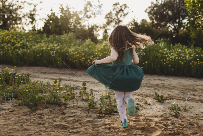 Little girl twirling her dress in backlight and field of flowers