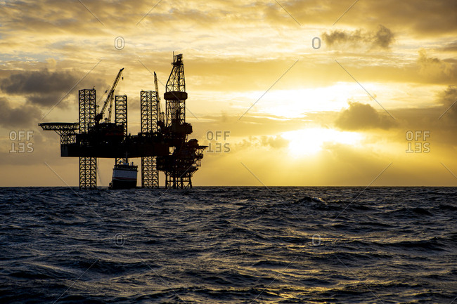Offshore drilling platform during sunrise with work vessel