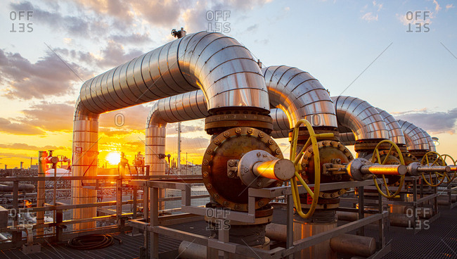 Sunset as viewed through pipe and vales in a refinery