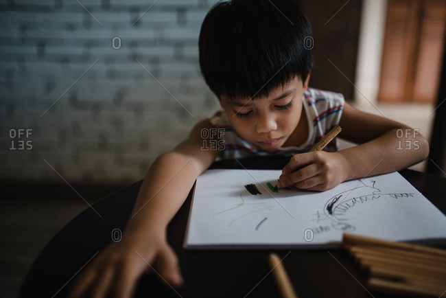 Asian boy drawing with color pencils
