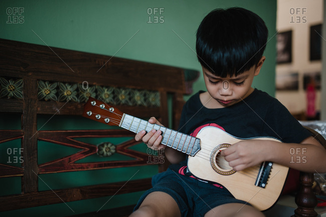 Asian boy playing guitar