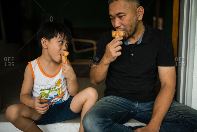Boy and father eating ice cream
