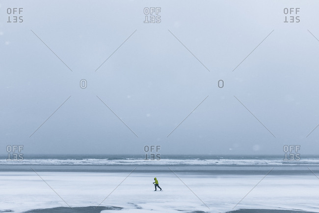 A lonely skier makes their way across a frozen beach in York, Maine