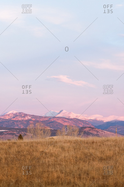 Beautiful Colorado sunrise with snow capped mountains and blue skies