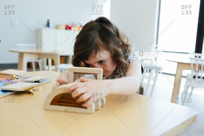 Little girl sits at table with toy and examines toy closely