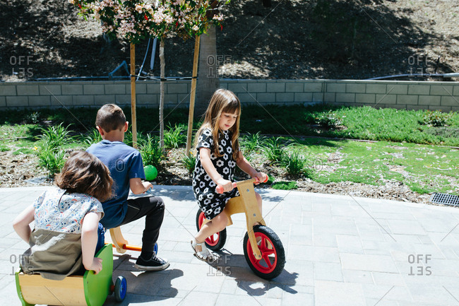 Kids outside play on wooden bicycles