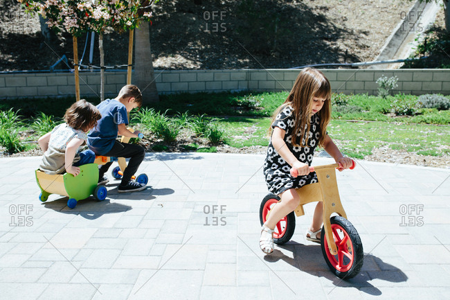 Three kids outside ride around on wooden bicycles