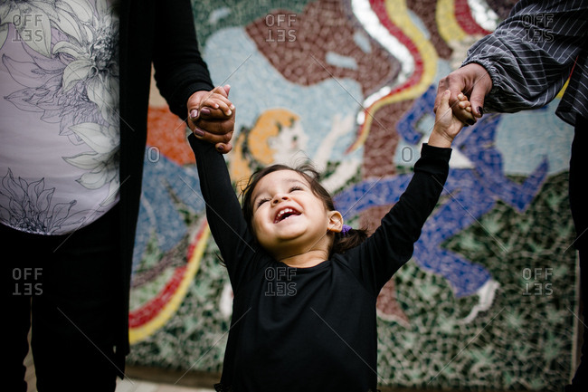 Little girl smiling and holding hands laughing in front of mural