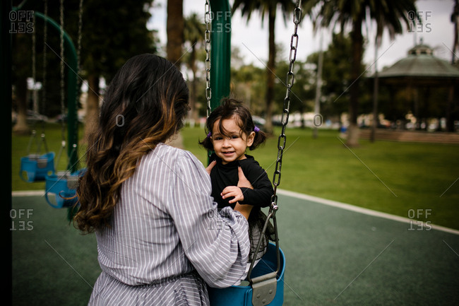 Mom putting daughter in swing at playground