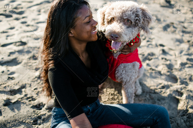 Young girl hugging labradoodle on beach at sunset