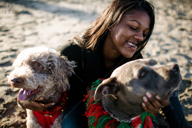 Young girl hugging and smiling at dogs on beach at sunset