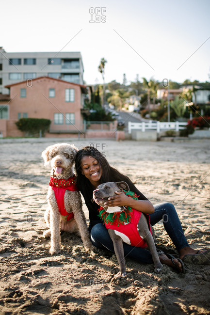Young girl smiling and hugging dogs on beach at sunset