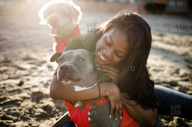 Young girl hugging pitbull on beach at sunset